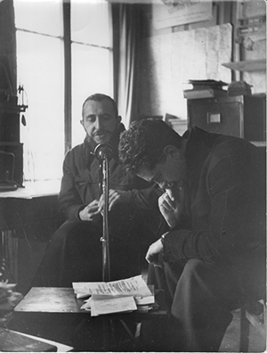Black and white image two men in front of a microphone during an AP Radio broadcast for Luxembourg and Neuilly-Plaisance, France.
